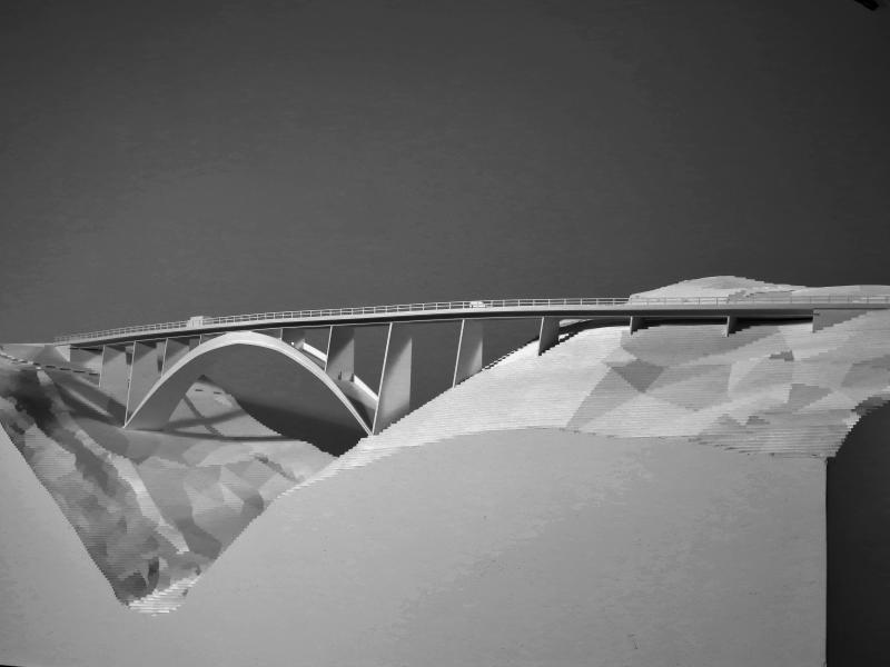 Der sichelförmige Bogen des Siegerprojekts spannt grosszügige 97.8m über den Bach. Somit stehen die Bogenkämpfer ausserhalb der Lawinenzone und öffnen den Blick ins Tal. Die Fahrbahn ist schlank und regelmässig
